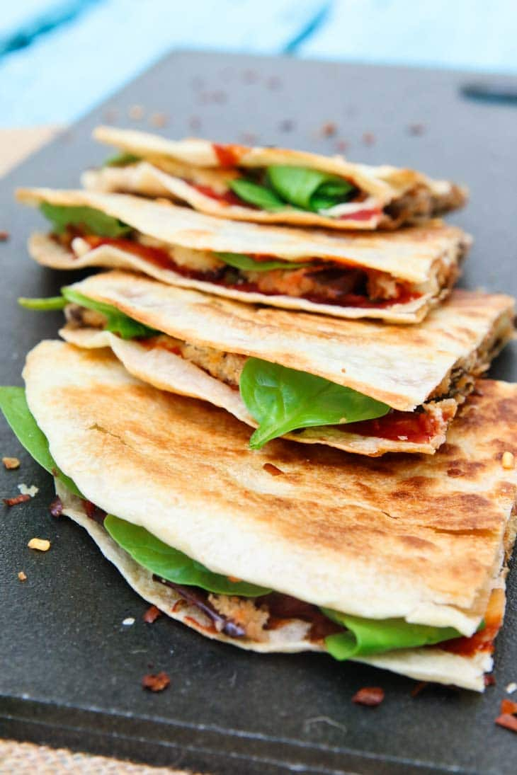 Vegan quesadillas with crispy grilled eggplant on a black surface