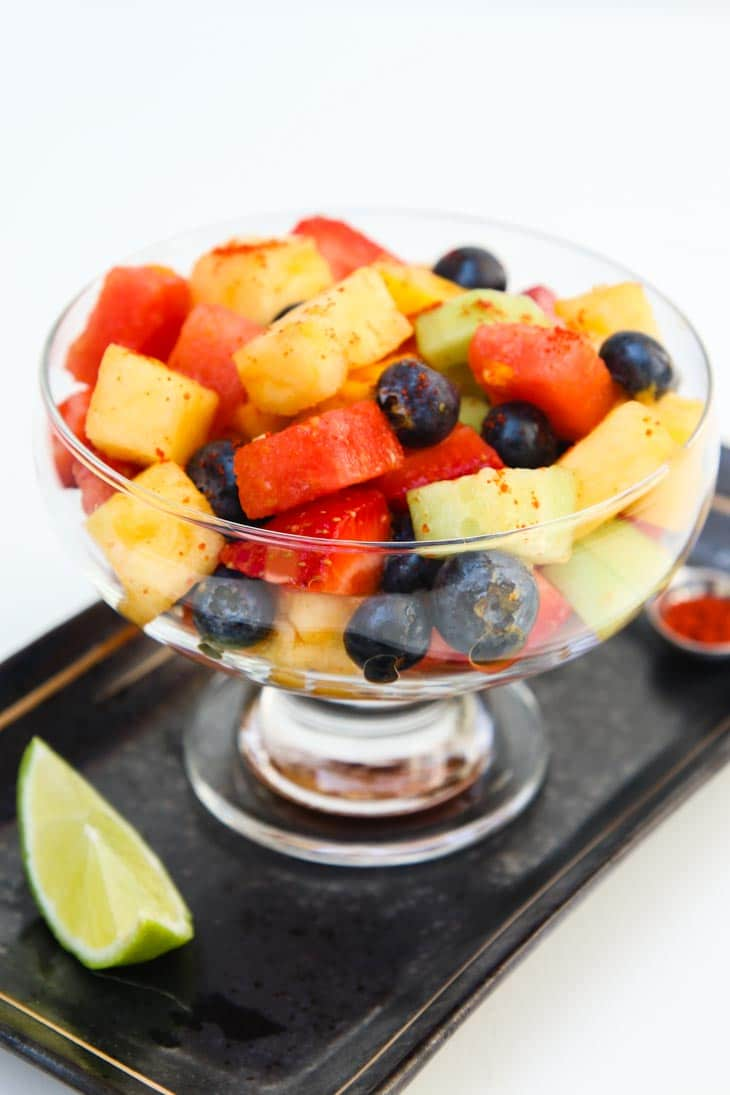 A large glass of homemade fruit salad on a tray with a lime wedge at the side