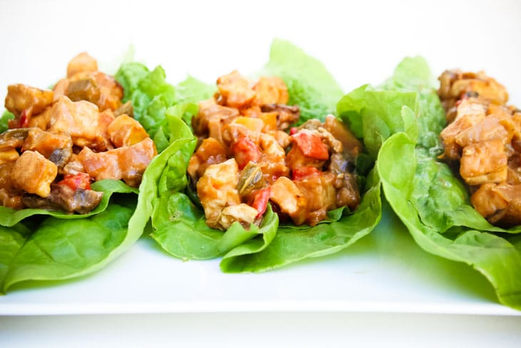 A side shot of tofu peanut lettuce cups on a white surface