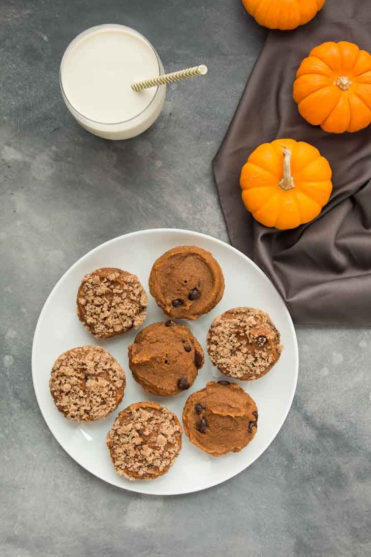 An overhead photograph of a plate of vegan pumpkin muffins with a glass of vegan milk and mini pumpkins off to the side.