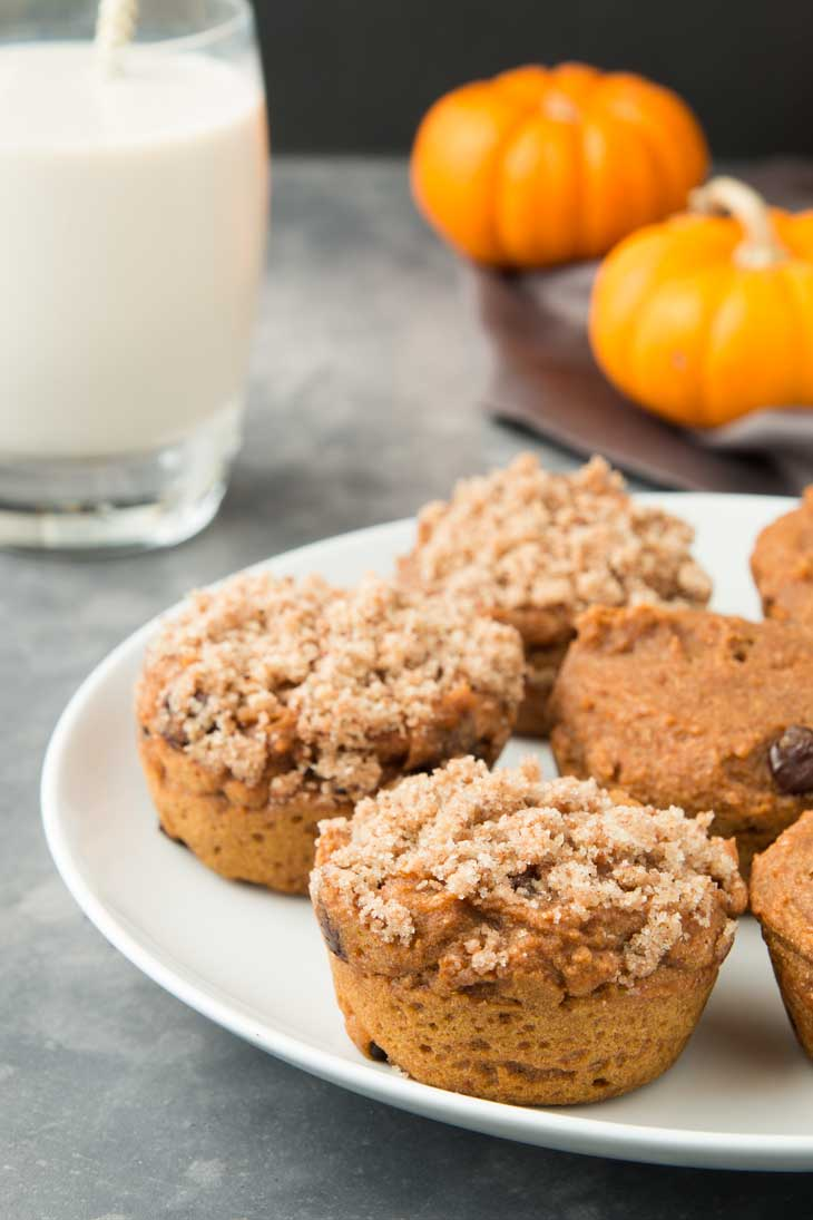 A side close-up of vegan pumpkin muffins on a white plate. There's a glass of milk and mini pumpkins in the background.