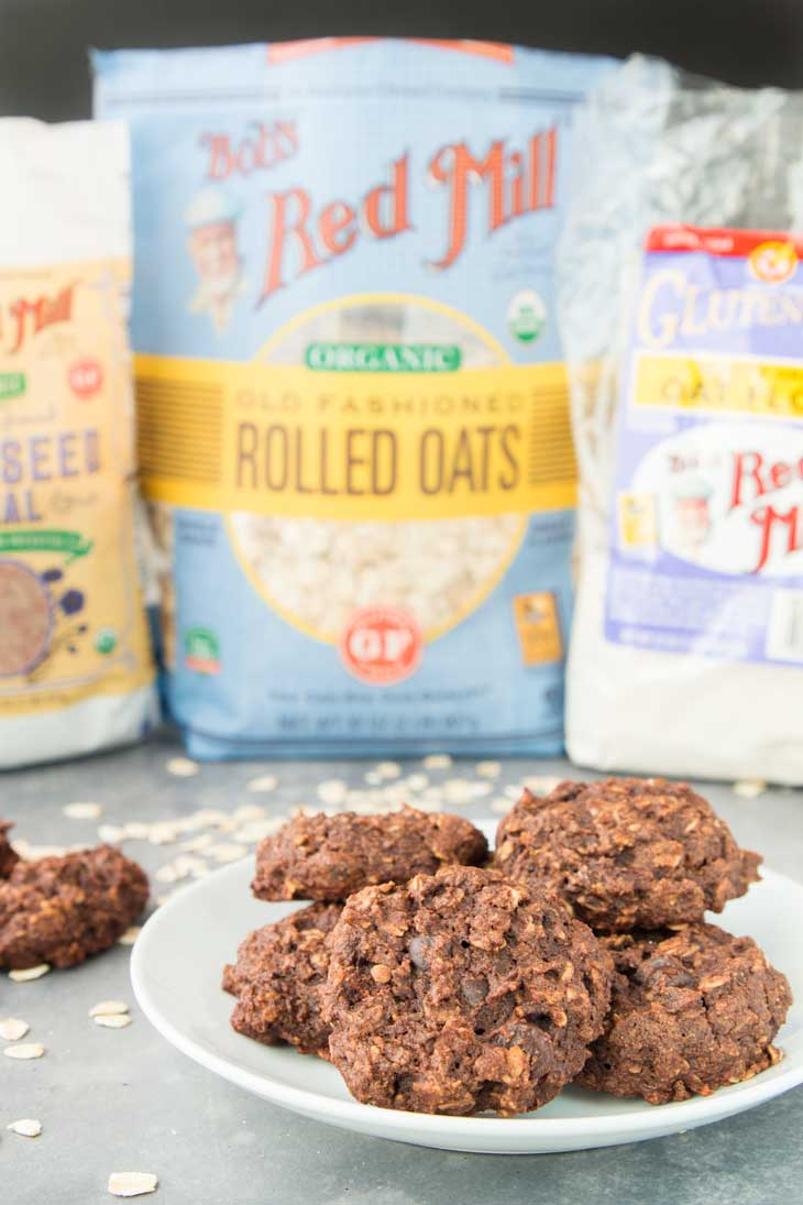 Side photograph of chocolate breakfast cookies on a white serving plate with bob's red mill products in the background.