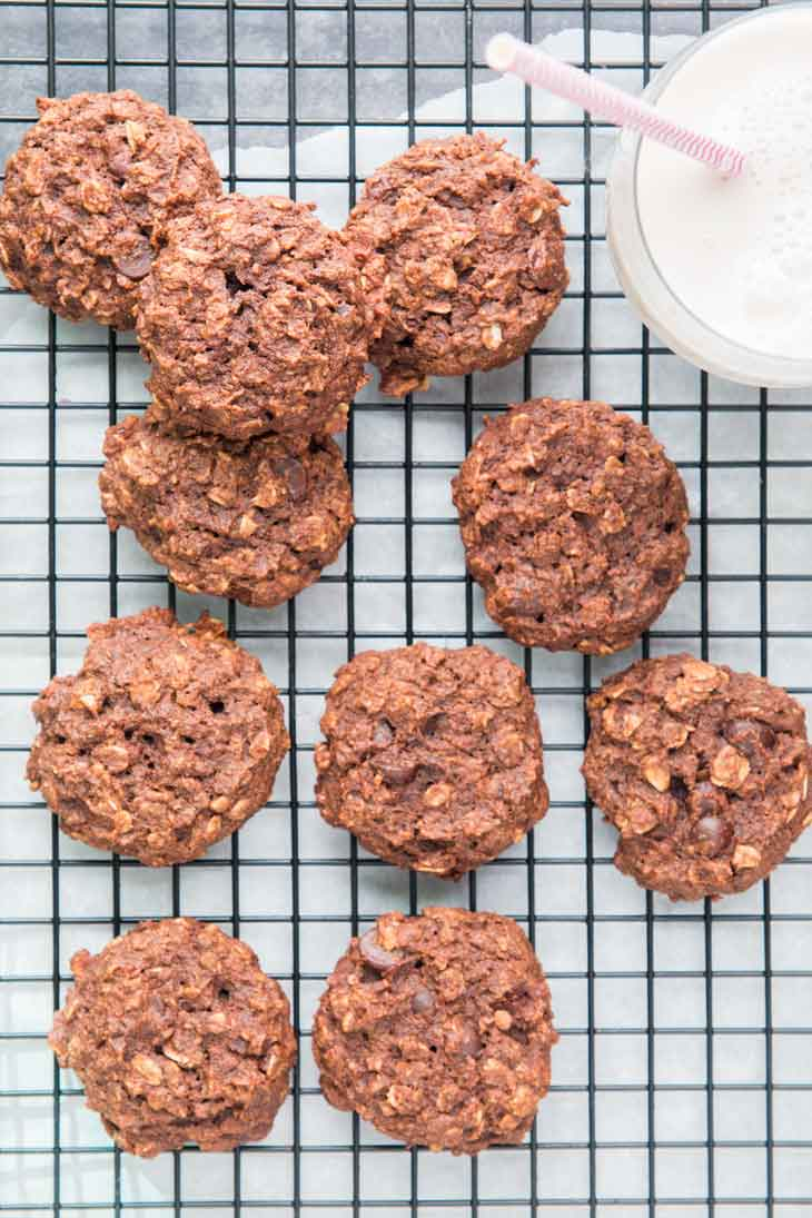 Overhead photograph of chocolate breakfast cookies cooling on a black cooling rack with a glass of milk off to the side.