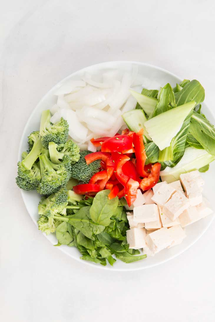 Overhead photograph of veggies in a white bowl being used for a healthy stir fry recipe.