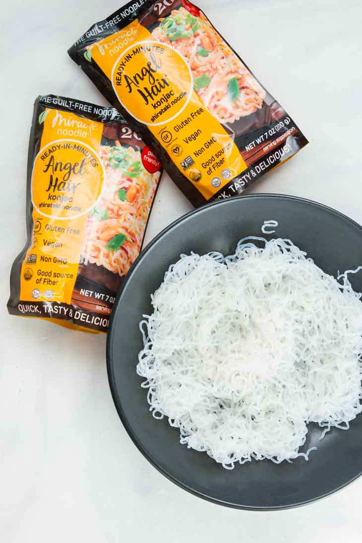 Overhead photograph of cooked miracle noodle angel hair in a bowl with packaging on the side.