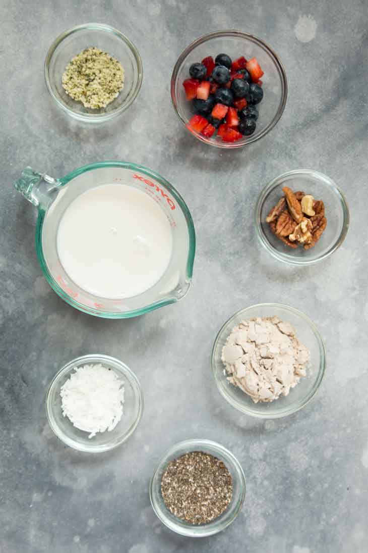 An overhead photograph of all the ingredients needed to make a vegan keto superfood breakfast bowl, including non-dairy milk, seeds, protein powder, mixed berries, and nuts.