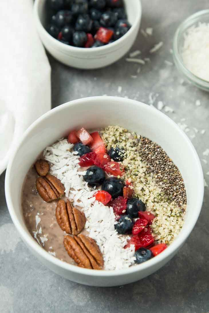 A 45 degree photograph of a vegan keto breakfast bowl. There's some shredded coconut and mixed berries in the background.