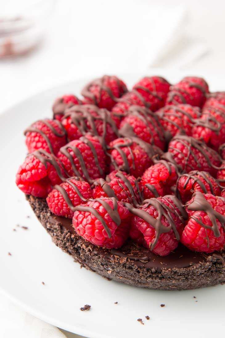 A side close up of vegan chocolate pie topped with raspberries and drizzled with chocolate.
