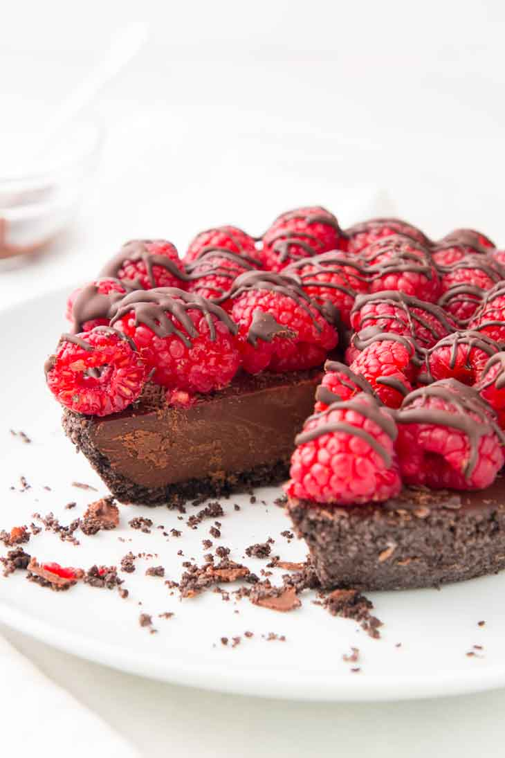 A side photograph of vegan chocolate pie with raspberries on top and drizzled with chocolate.