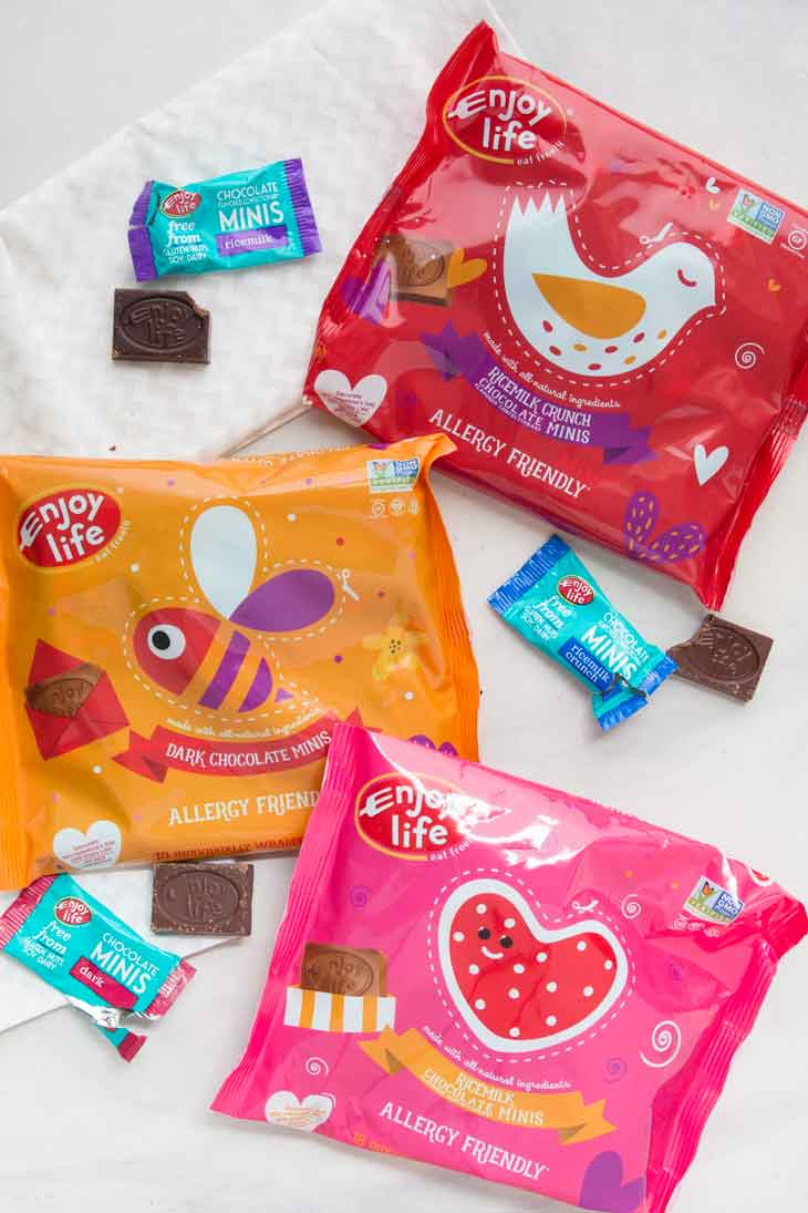 An overhead photograph of enjoy life foods valentines day mini chocolates. There are three different varieties and bags.