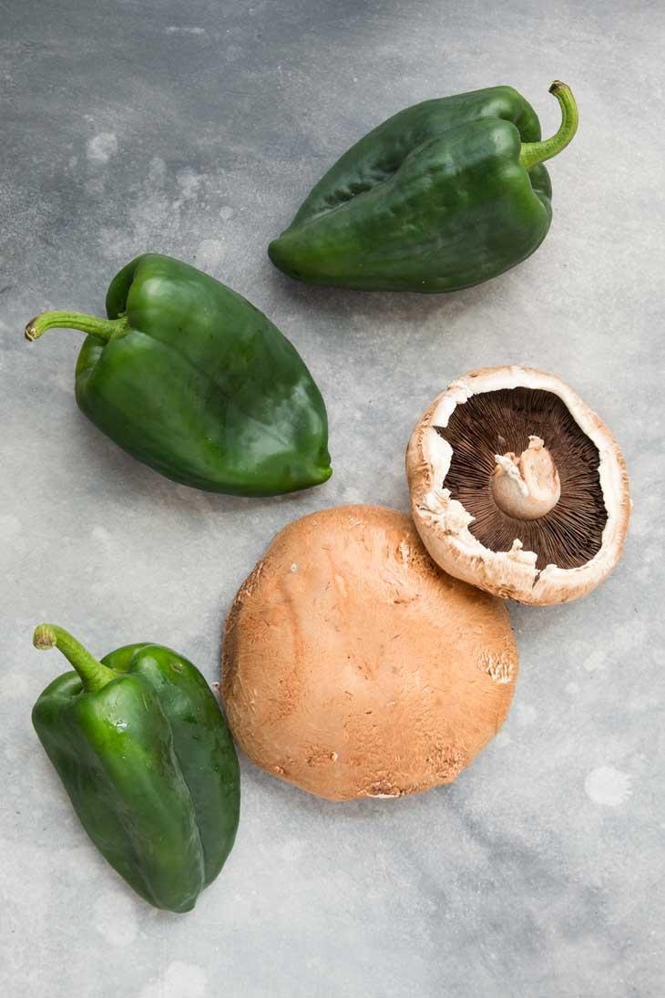 An overhead photograph of whole portobello mushrooms and poblano peppers going into vegan quesadillas.
