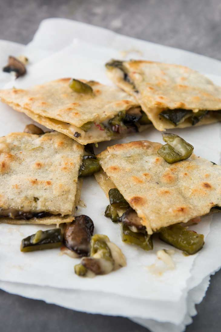 A side closeup of vegan quesadilla pieces stuffed with poblano peppers and mushrooms.