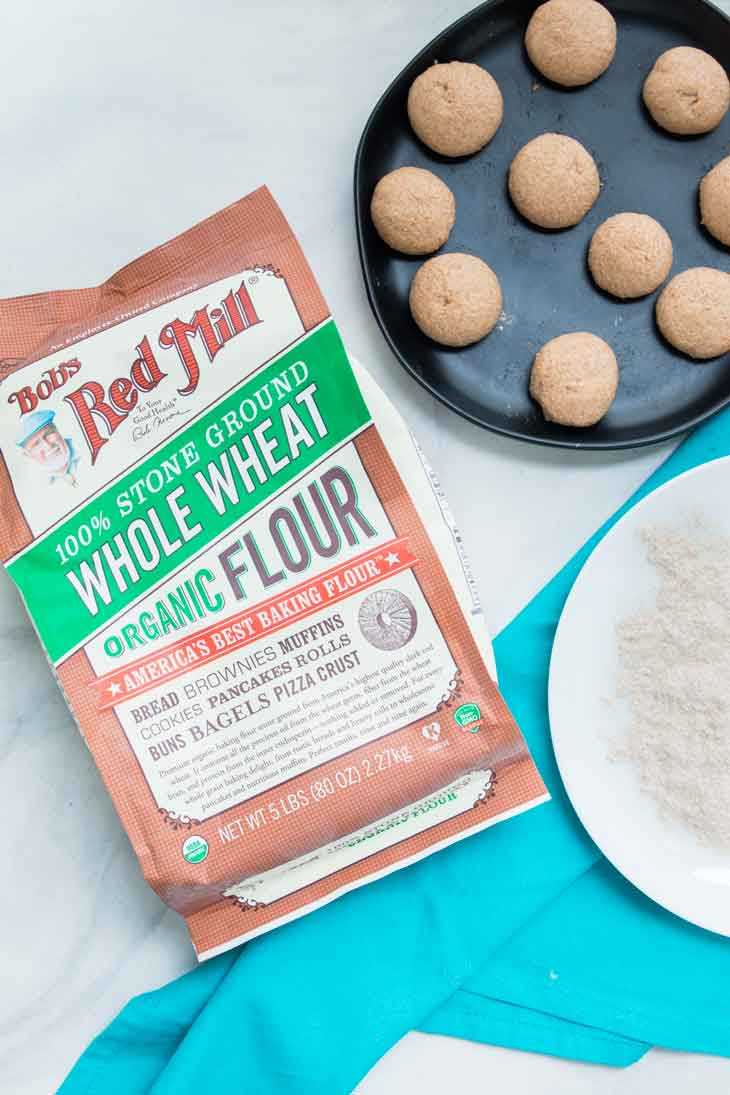 An overhead photograph of whole wheat flour and portioned dough for a roti recipe.