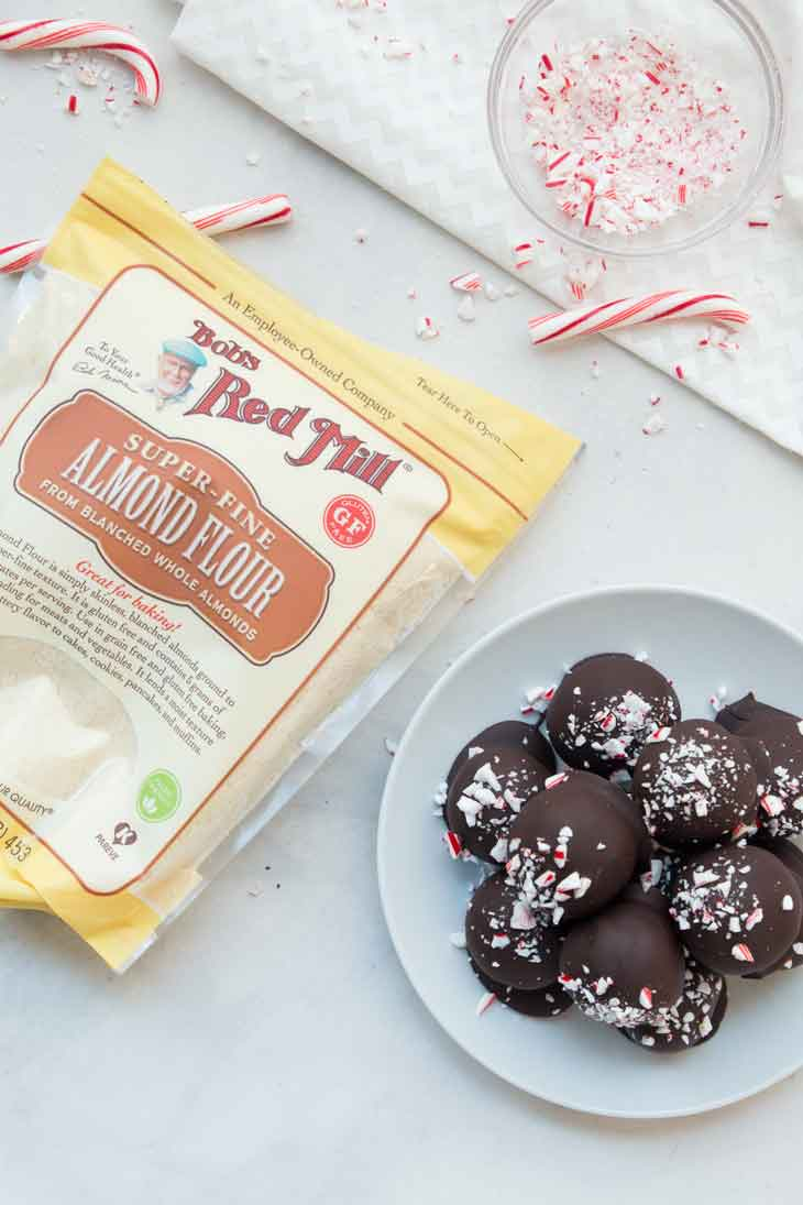 An overhead photograph of almond flour bag next to vegan gluten-free brownie truffles and candy canes.