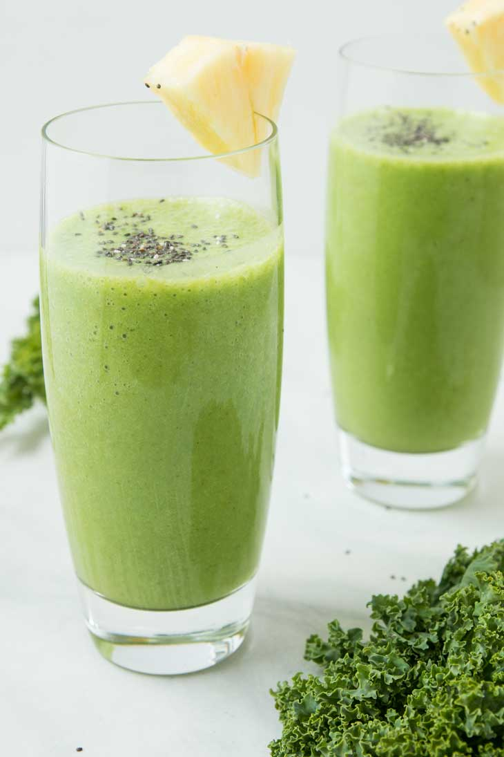 Two tall glasses of pineapple kale smoothie topped with chia seeds and a wedge of pineapple.